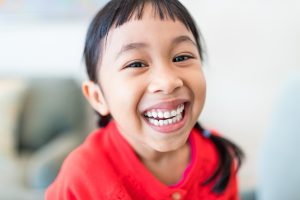 Happy, laughing little girl in red shirt